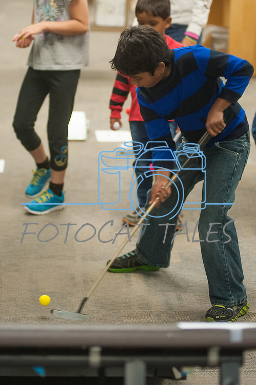 Sohan Vadlakunta attempts a ramp shot during the Mini Golf Night at the Carson City Library on Friday May 9, 2014. Kids and parents built a custom mini golf course throughout the library using anything at their disposal and engineering ideas to make a difficult course. Everything from tables to shelves were used to create creative courses.<br /> (Photo by Kevin Clifford/Nevada Photo Source)