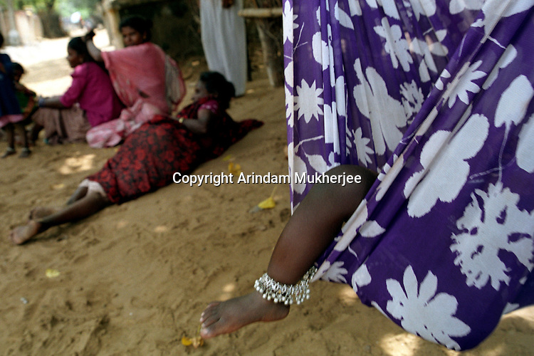 A little girl sleeps in a hammock while her mother and neighbours seek shade from the heat of the midday sun.Nagapattinam .India.