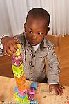 2 year old toddler boy at home making tower of alphabet blocks