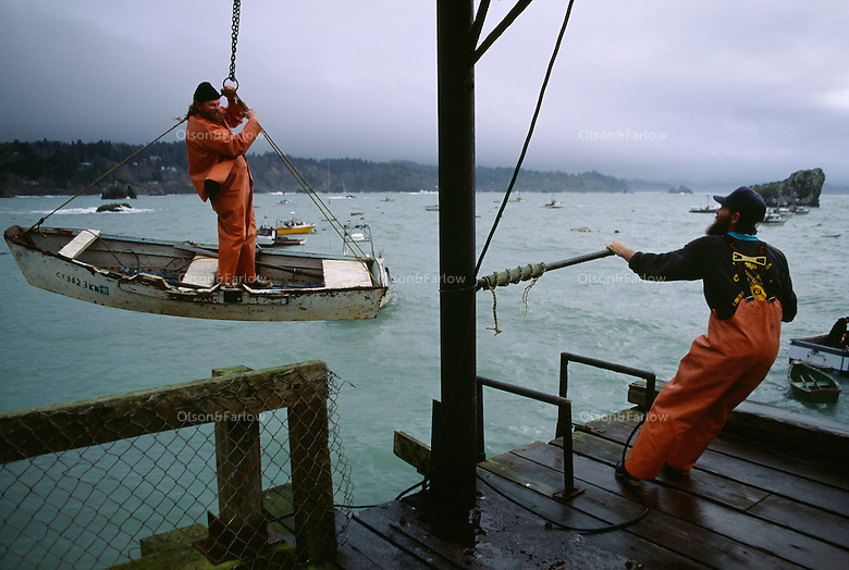 With help from a friend, a fisherman in a dingy dangles in the air as he is lowered by hand from the Trinidad pier to ocean waters 100 feet below. Crabbers can only get to their fishing boats tied up in the harbor in this method because of wind and storms.
