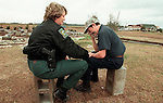 """Georgia Department of Natural Resourses Ranger Sue Furney (L) comforts Jaime Chong-Chaparro after an early morning tornado ripped through the Pine Level Community north of Cairo on Valentines Day killing his fiance who lived in the trailer that used to be located on the cinder blocks at left.  Furney came by and spotted Chong-Chaparro sitting on one of the cinderblocks from the completely destroyed trailer alone and stopped to listen to him tell of his love for his fiance.  """"She will be in my heart forever"""", said Chong-Chaparro, adding, """"she is with the angles."""""""