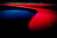 A fine art abstract and detail of a classic red Mercedes.  A curving shadow line across the hood separates brilliant red from black-blue shadows.
