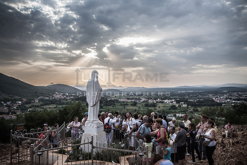 Faithful praying around the statue of the Virgin Mary, named locally as the 'Gospa' on the top of the Podbro, the hill of the apparitions. <br /> Bijakovici, Medjugorje, Bosnia and Herzegovina.
