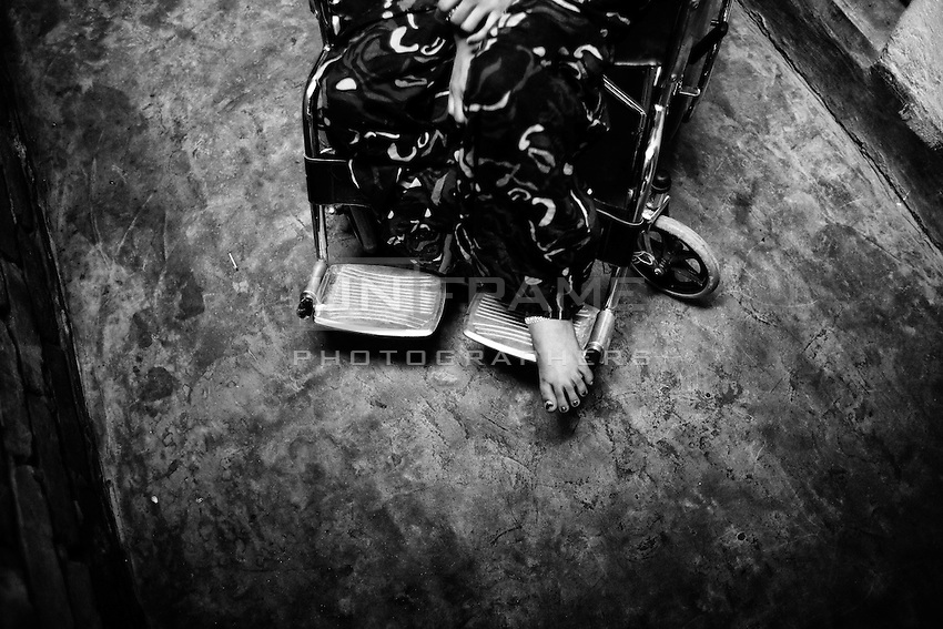 Aroti seeting on a wheelchair in her home, Savar, Near dhaka, Bangladesh.