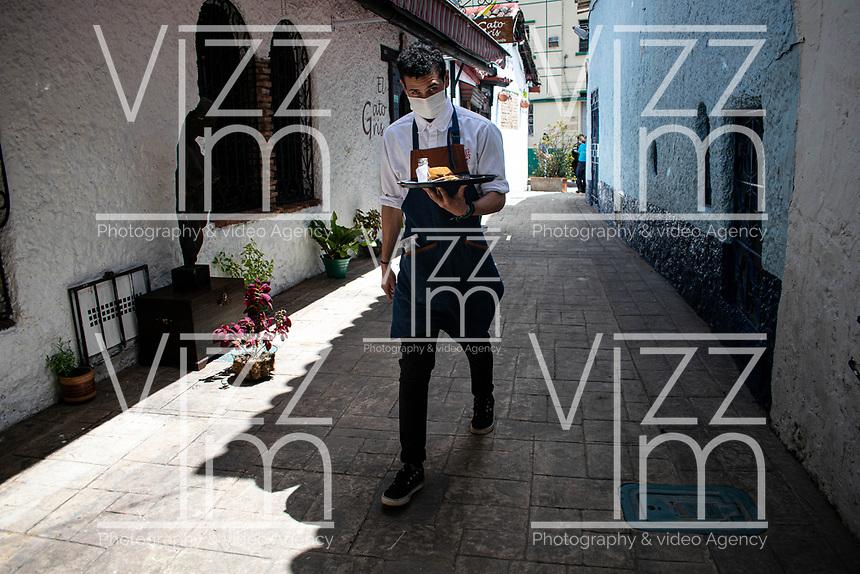 """BOGOTA - COLOMBIA, 05-09-2020: Un mesero lleva un pedido a los comensles durante el primer día del piloto de apertura de restaurantes y cafés al aire libre, denominado """"Bogotá a Cielo Abierto"""", en el Chorro de Quevedo en el centro de Bogotá que ahora tiene sus calles pintadas con formas geométricas en pintura neón y cuenta con mesas, distribuidas estratégicamente para mantener el distanciamiento físico al finalizar la cuarentena total en el territorio colombiano causada por la pandemia  del Coronavirus, COVID-19. / A waiter brings a peidod to the diners during the first day of the pilot for the opening of restaurants and outdoor cafes, called """"Bogotá a Cielo Abierto"""", in Chorro de Quevedo in the center of Bogotá, which now has its streets painted with geometric shapes in neon paint and has tables, strategically distributed to maintain physical distancing at the end of the total quarantine in the Colombian territory caused by the Coronavirus pandemic, COVID-19. Photo: VizzorImage / Johan Rugeles / Cont"""