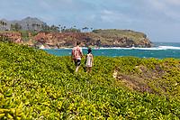 A man and a woman hike the Maha'ulepu Heritage Trail, Po'ipu, Kaua'i.