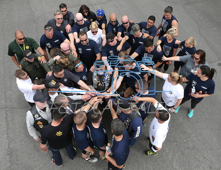 Carson City Sheriff's personnel surround Kevin Howell following the final leg of a 450-mile Nevada Law Enforcement Memorial Run from Las Vegas to Carson City, Nev. on Wednesday, May 4, 2016. Howell's son Carson City Sheriff's Dep. Carl Howell was killed in the line of duty in Aug. 2015.<br /> Photo by Cathleen Allison