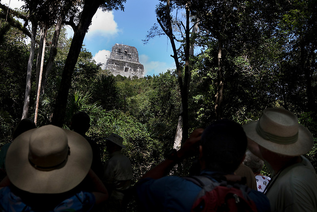 Tourists under a Mayan pyramid  at Tikal in the Mayan Biosphere.