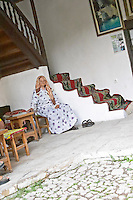 An old woman dressed in Muslim clothes sitting in a corner. The source of the Buna river and the house of the Whirling Dervishes, an old Muslim monastery, Blagaj. Federation Bosne i Hercegovine. Bosnia Herzegovina, Europe.