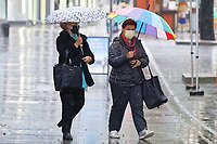 Pictured: Shoppers with umbrellas in the rain, Oxford Street, Swansea, Wales, UK. <br /> Re: A yellow warning has been forecast by the Met Office, from 6am until midnight on Saturday, for rain affecting south, west and parts of mid Wales, UK.