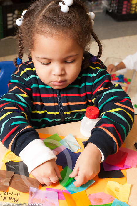 Education preschool 3-4 year olds art activity girl gluing squares of colored tissue paper to collage