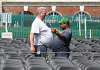 UVa worker celebrate with a belly bump after completing the set-up for graduation Thursday on the lawn of the University of Virginia.