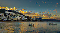 Fine Art Landscape Photograph morning sunrise of fishing boats in Banderas Bay in Puerto Vallarta Mexico.<br /> Golden sunbeams shimmering on the water as Pelicans become active and fishermen prepare for the beginning of another fishing day