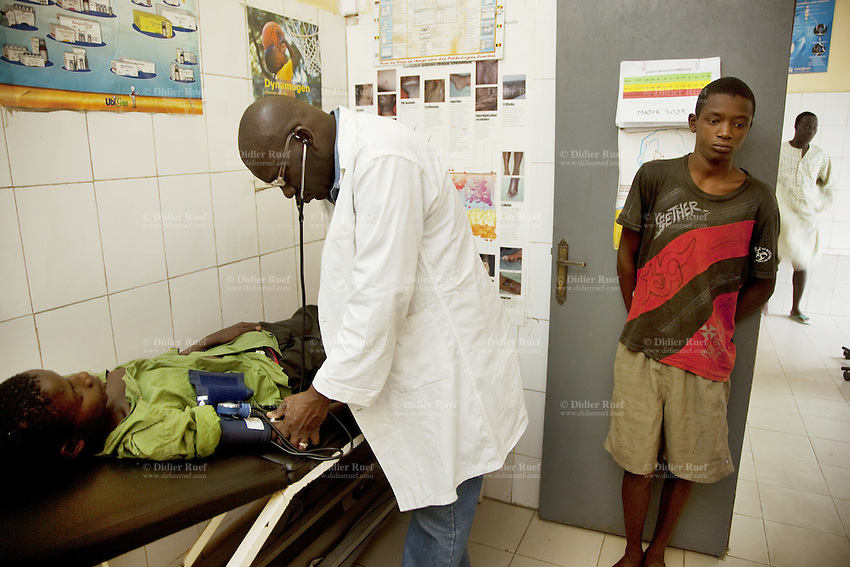 Senegal. Dakar. Rebeuss jail. In prison infirmary, medical officer Joseph Awanson (C) controls blood pressure to an inmate who was suffering from malaria. The Global Fund supports the malaria program with a financial grant. 06.12.09 © 2009 Didier Ruef / The Global Fund