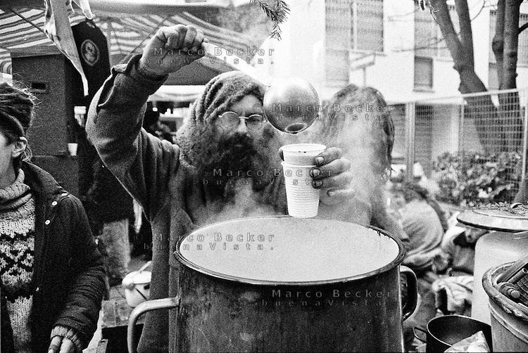 Milano, quartiere Sant'Ambrogio. Fiera degli Oh Bej! Oh Bej!, tradizionale mercatino del periodo natalizio milanese. Un uomo dalla folta barba serve con un mestolo un bicchiere di vin brulè da un pentolone fumante --- Milan, Sant'Ambrogio district. Oh Bej! Oh Bej!, traditional Milanese Christmas fair. A man with thick beard serving with a ladle a beaker of mulled wine from a big steaming pot