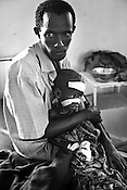 29-year-old Noor Gedu holds his 3 year malnutrioned son, Ali Noor Gedu  who weighs just 5.8kgs at the stabilization ward of the GIZ Main Hospital in the Dadaab refugee camp in northeastern Kenya. Photo: Sanjit Das/Panos