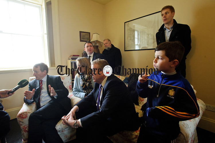 Young Mark Mc Grath tucks into the biscuits as Enda Kenny, Taoiseach, is interviewed for local media during his visit to Loop Head to launch the Fine Gael tourism initiative. Looking on are Clare candidates Councillor Mary Howard, Joe Carey, TD and Pat Breen, TD. Photograph by John Kelly.