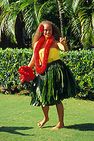 Hawaiian woman dances a hula in a ti leaf skirt with uli uli  ( gourd rattle) and red carnation lei