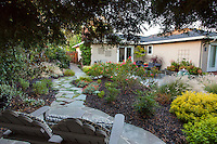 Small space garden with side yard entry path leading to secluded patio under trees, Lundstrom Garden, design by Susan Morrison