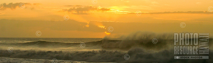 The sun begins to set behind a wave and clouds at Pipeline on Oahu's North Shore.
