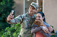 Happy US Army soldier and his wife, with puppy outside home, model-released, stock photo, DoD compliant, for sale, for advertising