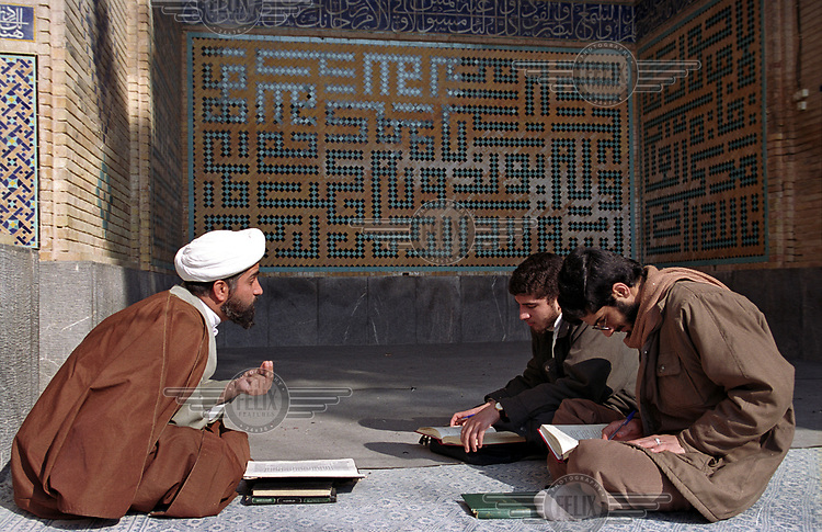 A mullah talks to studios during a religious education lesson at the Madraseh-ye Nimurvand.