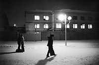 Ukraine. Province of Kiev. Chernigov. Night scene at the railway station. A woman walks on a snowy platform while a couple kisses. Chernigov is distant 120 km from the Chernobyl atomic power station. Many men and women working on two weeks shifts in the dead zone (30 km exclusion zone), created after the catastrophe which took place on april 1986 at 1.23 am with the explosion of reactor No 4 at Chernobyl atomic power station, live in the town of Chernigov. © 2006 Didier Ruef