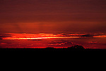 Sunset toward New Jersey from Mount Moses on Staten Island, NY.  Blazing Sun with highlighted red, orange and yellow clouds