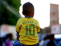 A young boy wearing a Neymar Jnr Brazil shirt sits on his fathers shoulders as he tries to get a peek of his side during training ahead of tomorrow's World Cup quarter final vs Colombia