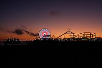 The Santa Monica Pier at lit up at dusk.