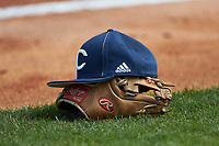 A Catawba Indians cap sits on top of a Rawlings baseball glove between innings of the game against the Queens Royals during game one of a double-header at Tuckaseegee Dream Fields on March 26, 2021 in Kannapolis, North Carolina. (Brian Westerholt/Four Seam Images)