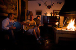Three men playing Brazilian music and singing around a fire in the lounge of Rio do Rastro Eco Resort, Santa Catarina, Brazil