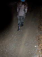 Person walking away from camera down country road<br />