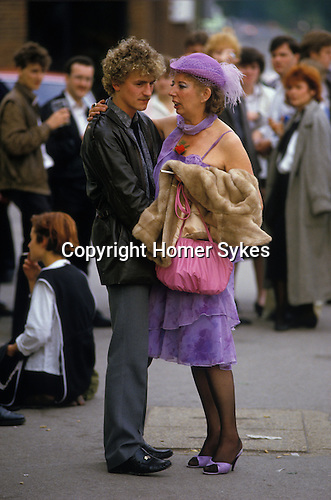 Ascot, Berkshire. 1980's<br /> At Royal Ascot, a cougar couple enjoy a quite chat after a day at the races. She whispers to him, as he rocks back on his heals. Stylish in a new lavender ensemble and eye shadow to match. A single red rose, displayed in her cleavage that traditionally symbolising love and strong emotions.