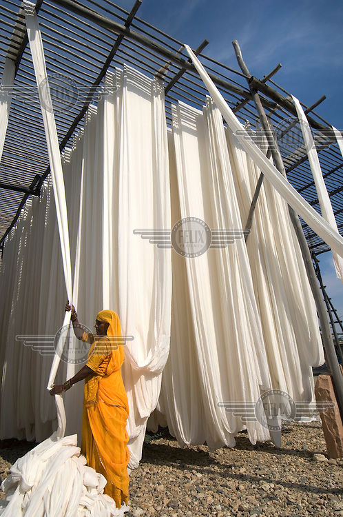 Lengths of sari dry on bamboo drying racks. This centre is the most prolific in India for the dying and printing of saris reaching markets all over the country.