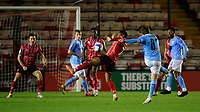 Lincoln City's Tayo Edun blocks a shot from Manchester City U21's Adrian Berbnabe<br /> <br /> Photographer Chris Vaughan/CameraSport<br /> <br /> EFL Papa John's Trophy - Northern Section - Group E - Lincoln City v Manchester City U21 - Tuesday 17th November 2020 - LNER Stadium - Lincoln<br />  <br /> World Copyright © 2020 CameraSport. All rights reserved. 43 Linden Ave. Countesthorpe. Leicester. England. LE8 5PG - Tel: +44 (0) 116 277 4147 - admin@camerasport.com - www.camerasport.com