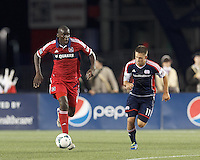 Chicago Fire defender Bakary Soumare (4) brings the ball forward as New England Revolution midfielder Kelyn Rowe (11) closes. In a Major League Soccer (MLS) match, the New England Revolution (blue) defeated Chicago Fire (red), 2-0, at Gillette Stadium on August 17, 2013.