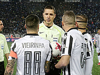 Pictured: Match referee Alexandros Aretopoulos (C) at Toumba Stadium in Thessaloniki, Greece. Sunday 25 February 2018<br /> Re: Sunday's Greek Super League derby between PAOK Thessaloniki and Olympiakos was called off after Olympiakos' manager Oscar Garcia was struck in the face by an object believed to be a till machine paper roll, thrown by a spectator minutes before kick-off.<br /> Garcia left Toumba Stadium for a local hospital to seek treatment for a bloodied lip.<br /> The incident prompted the Olympiakos team to leave the pitch in protest before riots erupted outside the ground.<br /> Angry PAOK fans leaving the stadium then clashed with police who used tear gas to quell the violence.