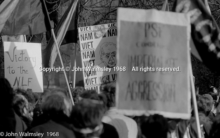 """Placards, including one showing Harold Wilson, the British Prime Minister at the time, at the anti-Vietnam war demonstration march from Trafalgar Sq to Grosvenor Sq Sunday 17th March 1968.  The Vietcong flag is held aloft.  A banner says """"Victory to the NLF"""".  The Vietcong (National Liberation Army, NLF) was a political organisation and guerrilla army in South Vietnam which fought the Americans."""