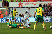 Saturday, 29 March 2014<br /> Pictured: Michu of Swansea (C) is brought down by Ryan Bennett of Norwich (L)<br /> Re: Barclay's Premier League, Swansea City FC v Norwich City at the Liberty Stadium, south Wales, UK.