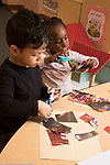 Eucation Preschool 3 year olds boy and girl cutting magazine pages with scissors