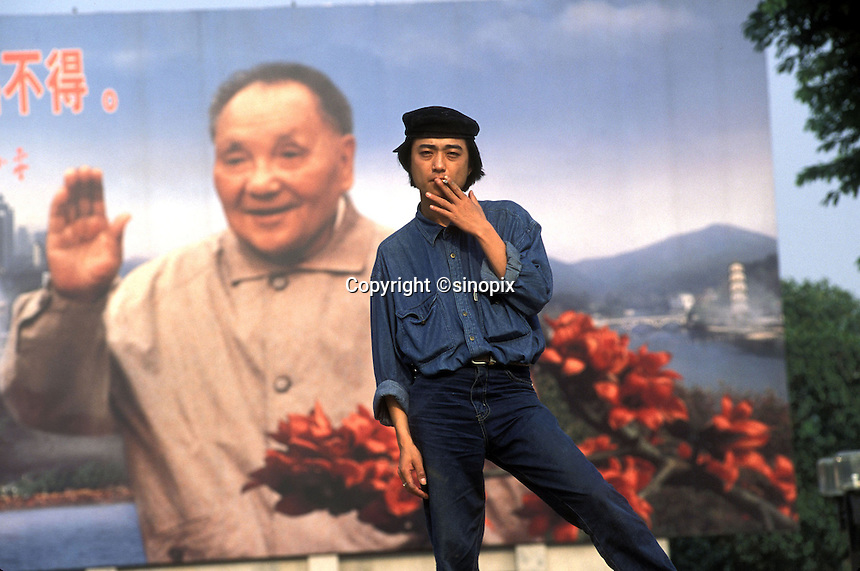 A young Chinese artist smokes a cigarette in front of a billboard of Deng Xiaoping in Guangzhou, China.