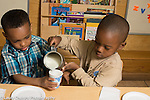 Preschool 3-4 year olds meal time boy pouring milk for classmate