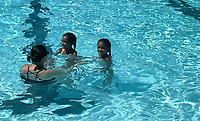 Faith Johnson of Fayetteville swims with her daughters Tiara Johnson (right) and Ciara Johnson, both 4, Monday Sept. 6, 2021 at Wilson Pool at Wilson Park in Fayetteville. Labor Day marks the end of the season at the pool. For information about Fayetteville parks see https://www.fayetteville-ar.gov/150/Parks-Recreation Visit nwaonline.com/210000907Daily/ for more photos. (NWA Democrat-Gazette/J.T. Wampler)