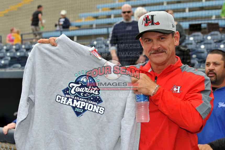 Former Asheville Tourists manager and current Texas Rangers roving instructor Joe Mikuliks displays his 2012 Sally League championship sweatshirt before a game between the Hickory Crawdads and the Asheville Tourists at McCormick Field on April 17, 2013 in Asheville, North Carolina. The Crawdads won the game 6-5. (Tony Farlow/Four Seam Images).