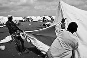 Strong winds blow and workers struggle as they pitch the newly arrived UNHCR tents in IFO extension camp in Dadaab, world's largest refugee camp in Eastern Kenya. Photo: Sanjit Das/Panos