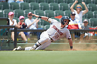Evan Skoug (11) of the Kannapolis Intimidators slides to the ground after rounding third base during the game against the Hagerstown Suns at Kannapolis Intimidators Stadium on July 17, 2018 in Kannapolis, North Carolina. The Intimidators defeated the Suns 10-9. (Brian Westerholt/Four Seam Images)