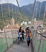 India, Rishikesh.  Footbridge over the Ganges (Ganga), Tera Manzil Hindu Temple in left background, holding numerous shrines to various Hindu gods.