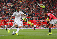 Pictured L-R: Gylfi Sigurdsson of Swansea against Tyler Blackett of Manchester, provides the cross to Ki Sung Yueng (not pictured) which he scored as his opening goal. Saturday 16 August 2014<br /> Re: Premier League Manchester United v Swansea City FC at the Old Trafford, Manchester, UK.