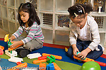 Preschool 3-4 year olds two girls playing separately with colorful plastic construction toys horizontal